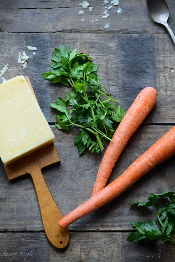 A photo of ingredients for potato soup, including cheese, parsley, and carrots.