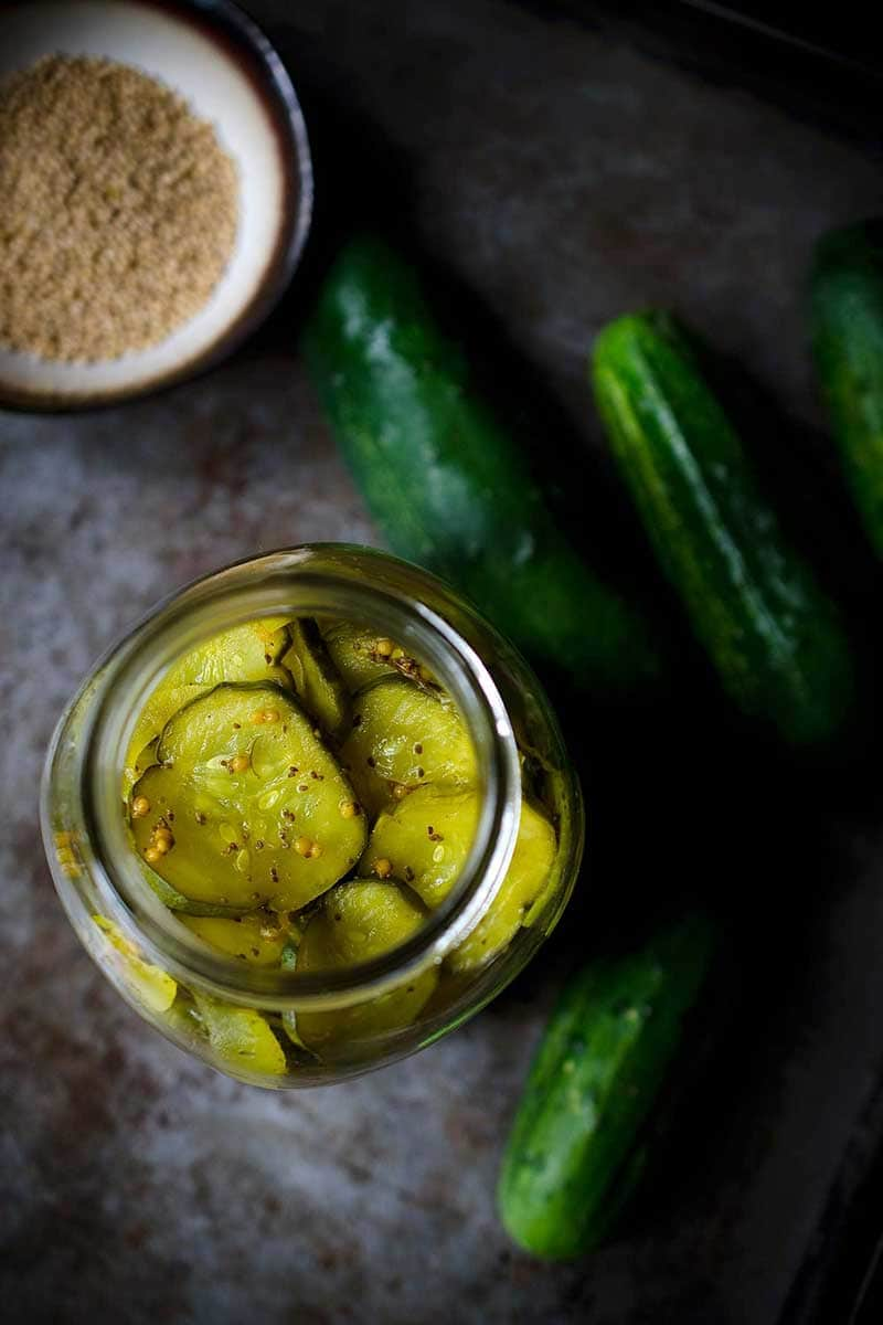 Overhead photo of bread and butter pickles recipe next to mustard seeds and cucumbers