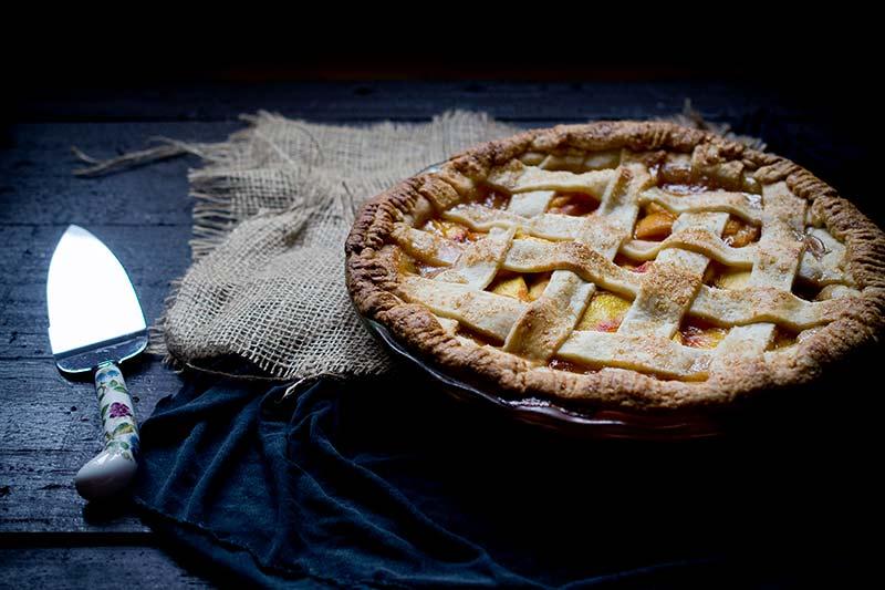 Homemade nectarine pie, uncut, on a burlap sac next to a pie cutter