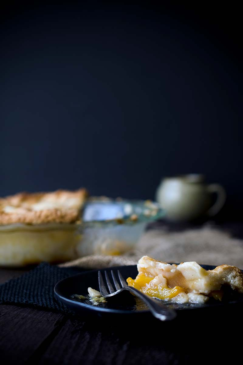 A slice of nectarine pie on a plate with a fork. Pie in dish in the background