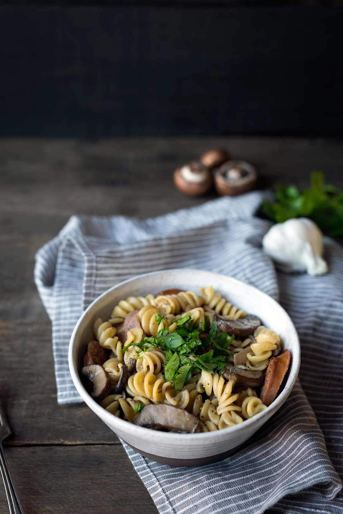 Closeup of mushroom pasta topped with parsley, surrounded by mushrooms and garlic.