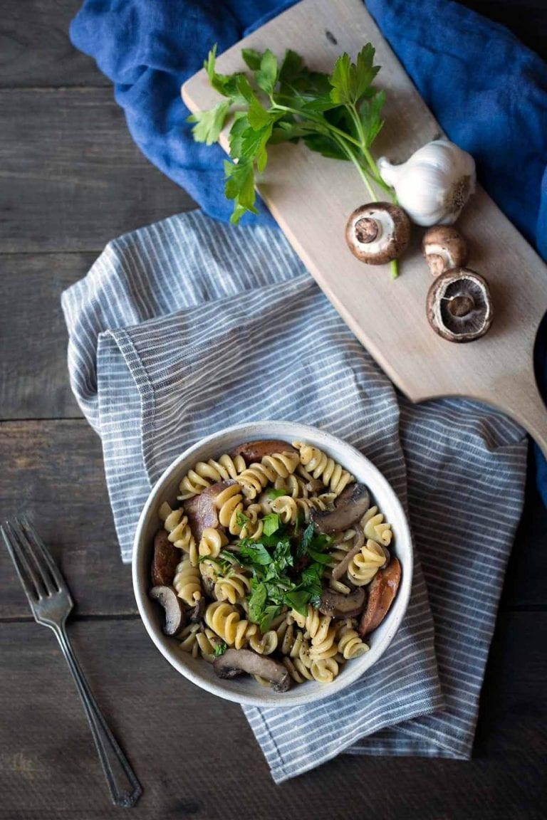 Sausage mushroom pasta in a bowl, sitting on a napkin.