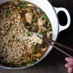 easy homemade ramen in a Dutch oven with chopsticks lifting the noodles