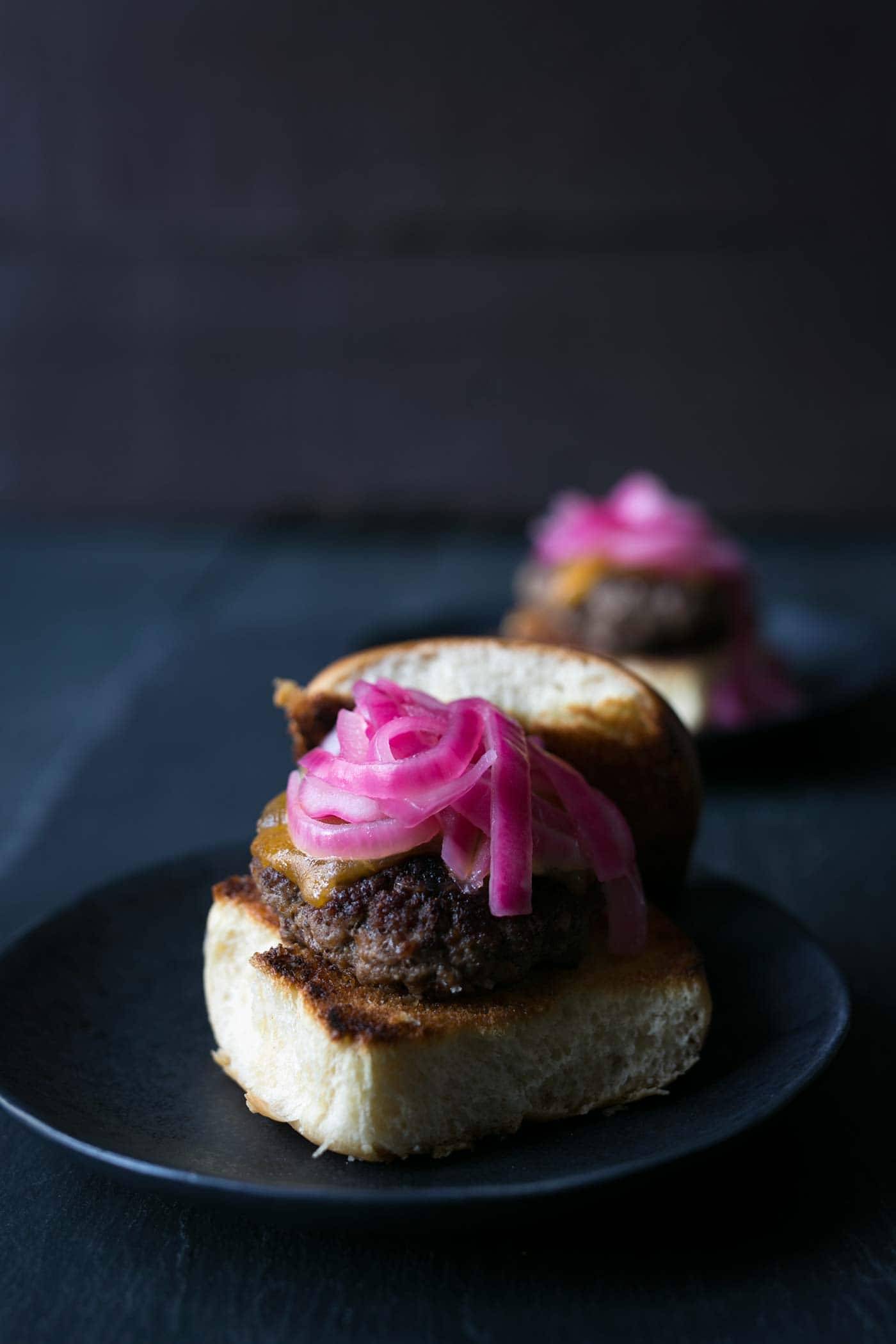 These Cheeseburger Sliders with Quick Pickled Onions are the PERFECT combinations of flavors and texture. They are also so easy to make! Get the recipe from SavorySimple.net.