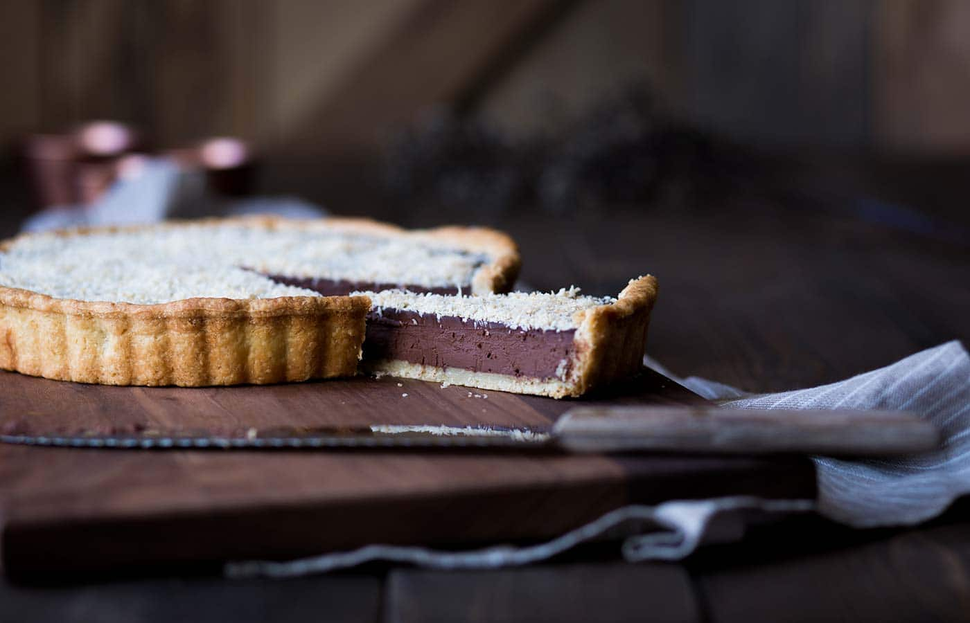 A slice of chocolate tart separated from the full tart.