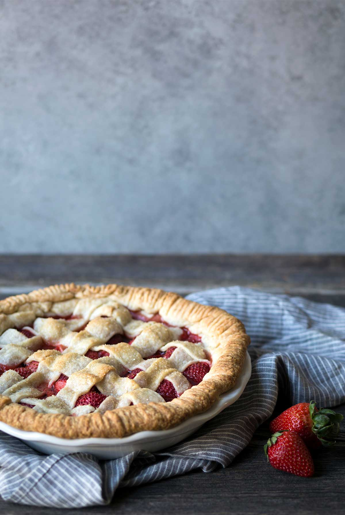 Fresh strawberry pie with a lattice top, sitting on a blue toned napkin next to fresh strawberries.