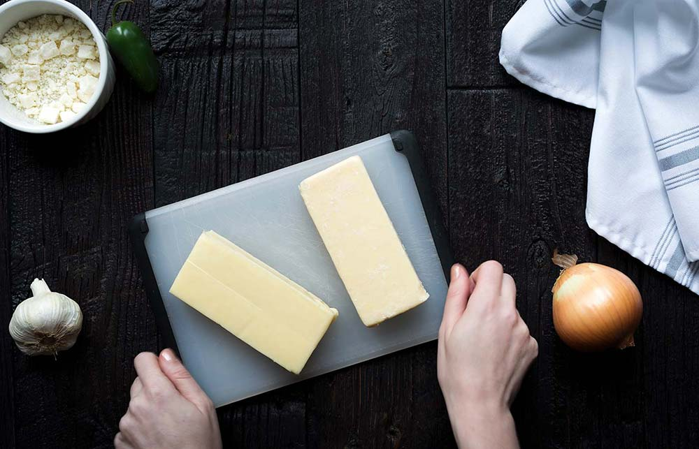 blocks of cheese on a cutting board