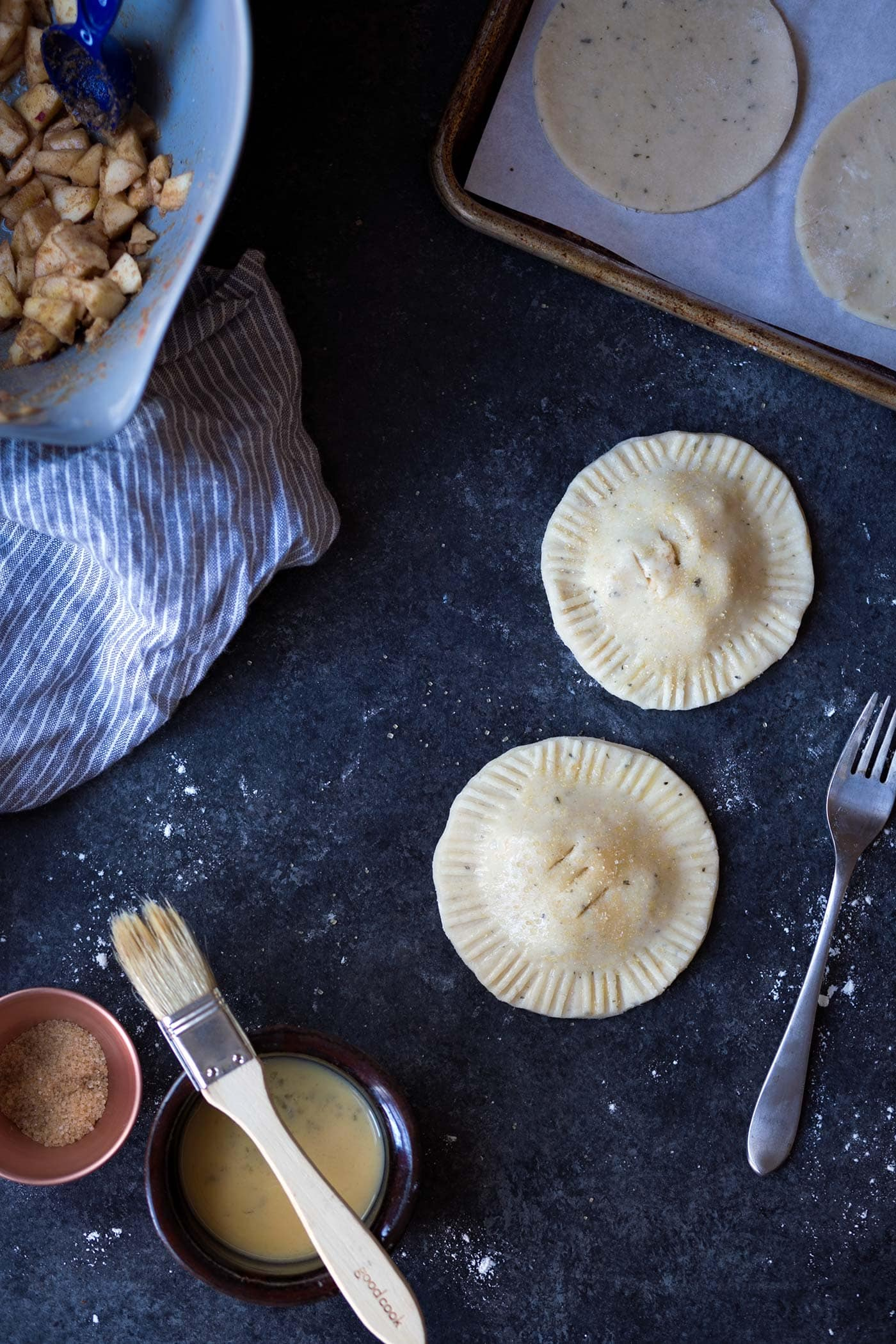 These apple hand pies have a delicate crust seasoned with fresh rosemary and thyme. They're a fragrant treat that will make your kitchen smell amazing! SavorySimple.net