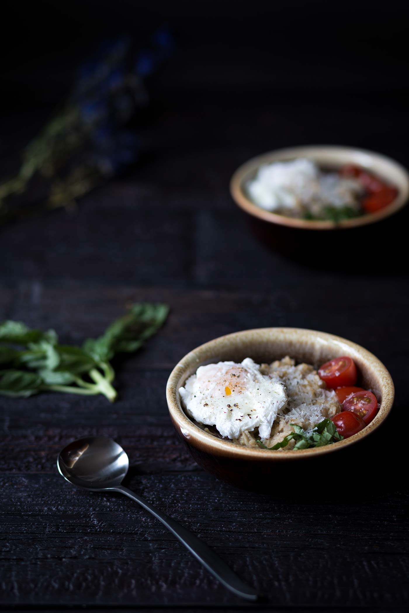 bowls of savory oatmeal with egg and tomatoes on a dark background