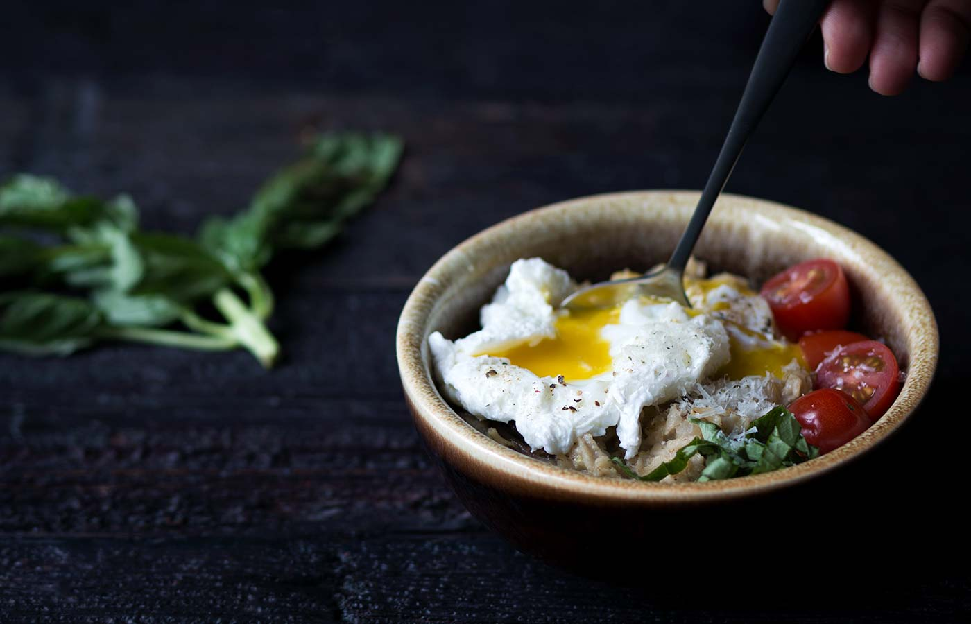 spoon breaking poached egg yolk in a bowl of cooked oats, tomatoes, and fresh basil