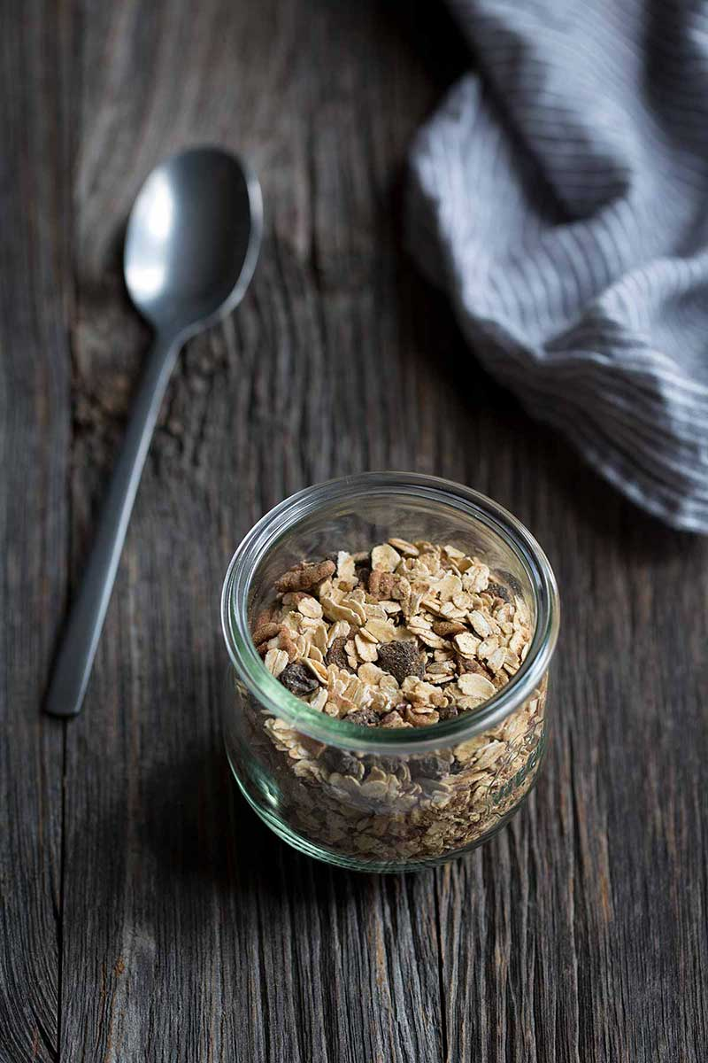 homemade muesli cereal in glass jar next to spoon