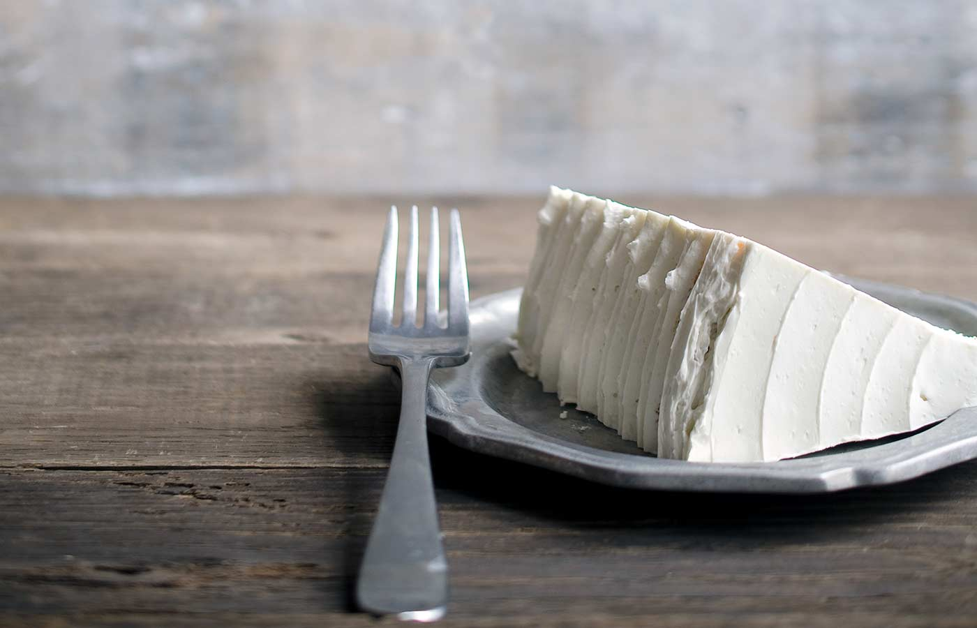 A slice of layer cake frosted with Italian Meringue Buttercream