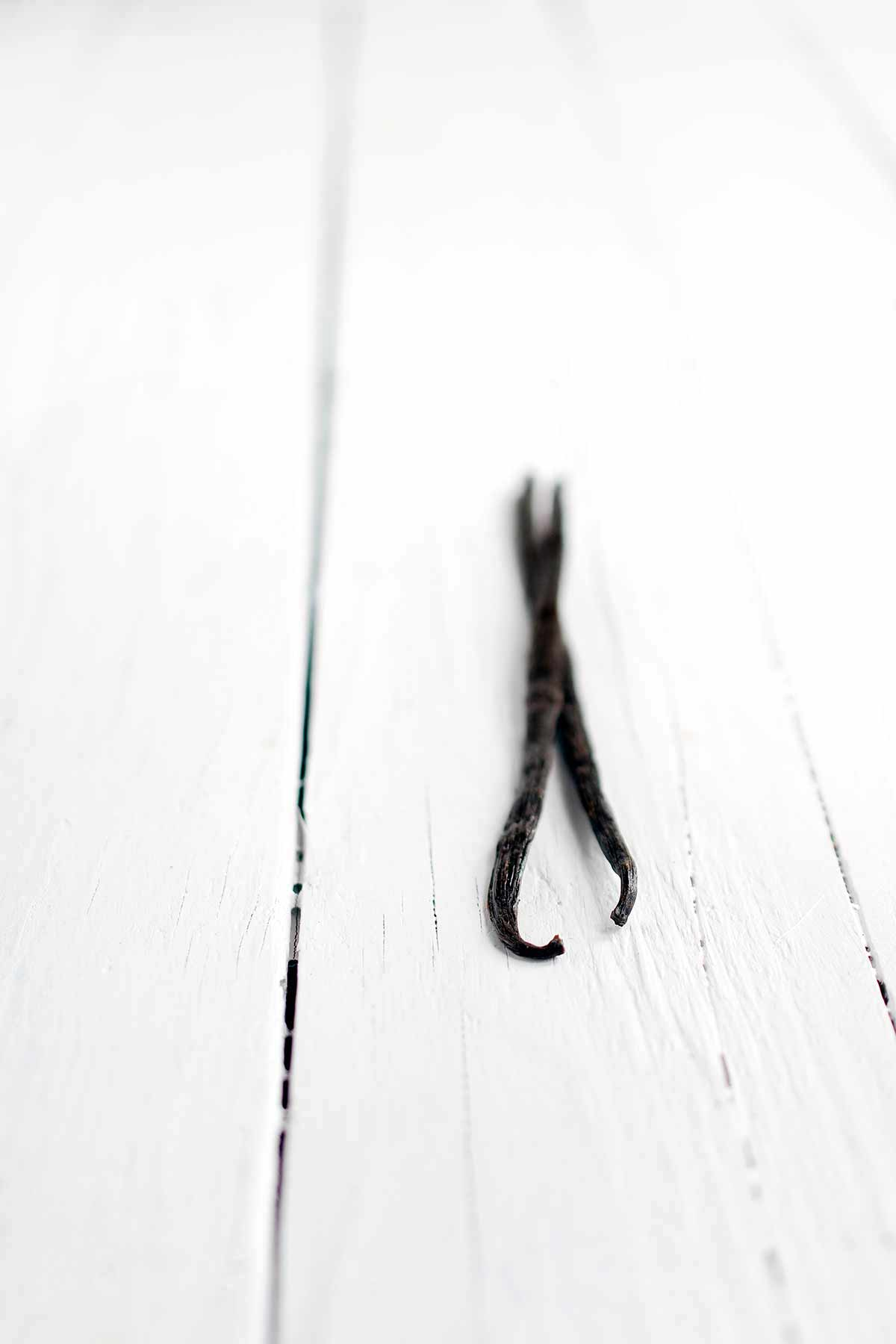 Two vanilla beans on a white backdrop.