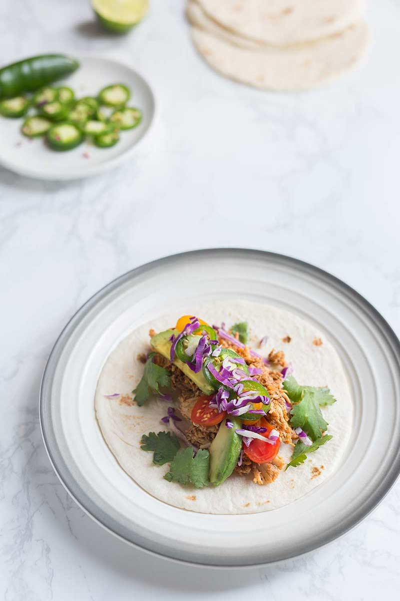 A rotisserie chicken taco recipe on a plate, surrounded by fixings. Marble backdrop.