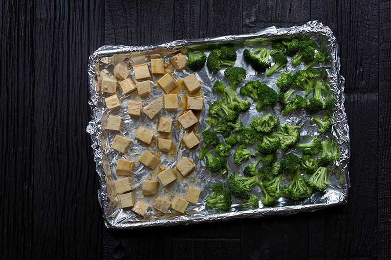 A photo of marinated tofu and broccoli on a foil-lined baking sheet, ready to be baked.