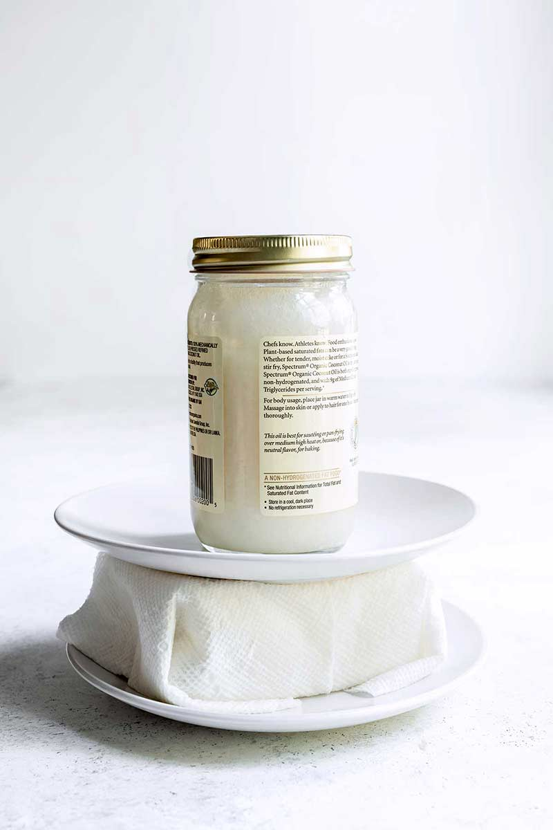 Tofu wrapped in paper towels and set between two plates, with a jar sitting on top