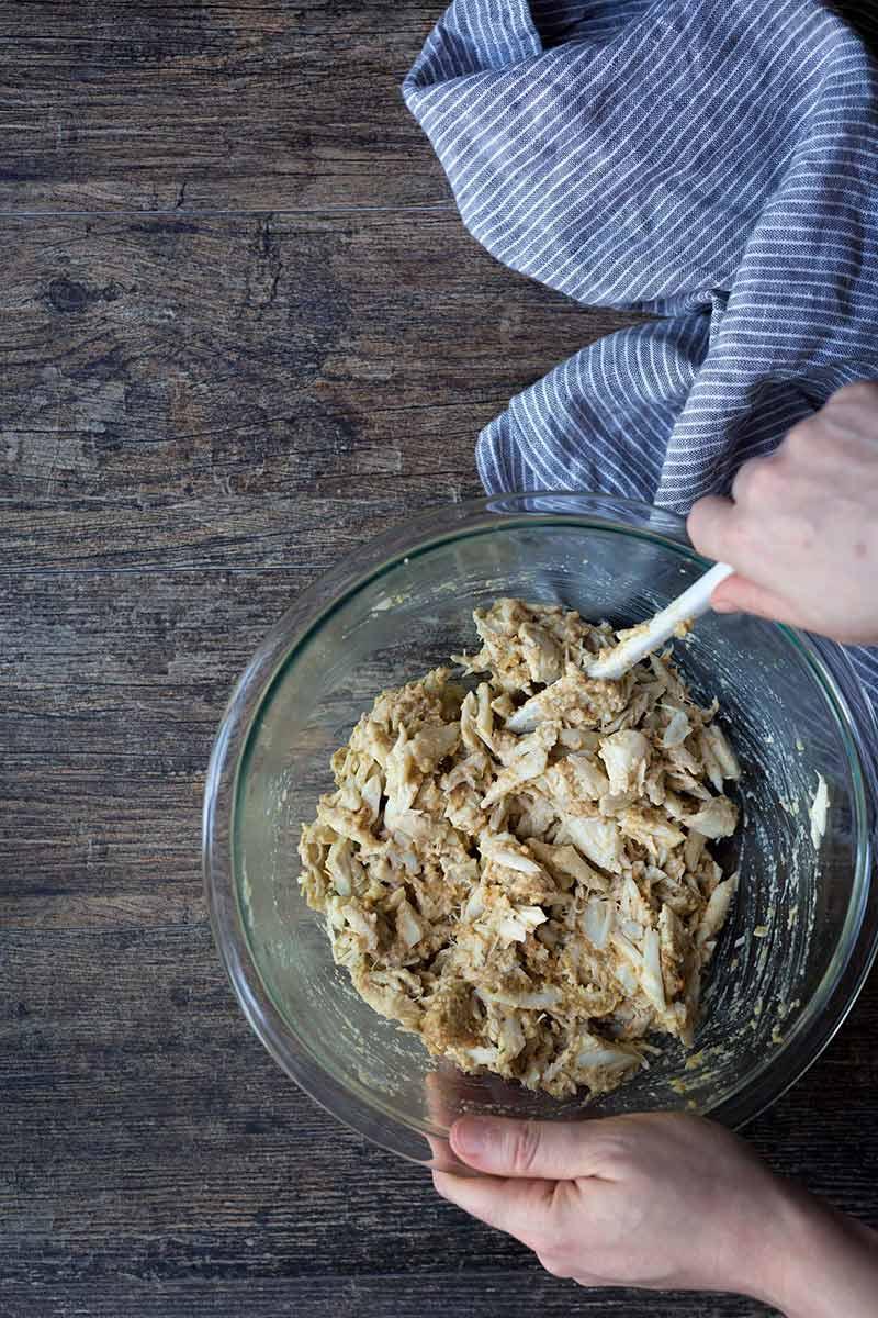 Stirring lump crab meat with crab cake ingredients