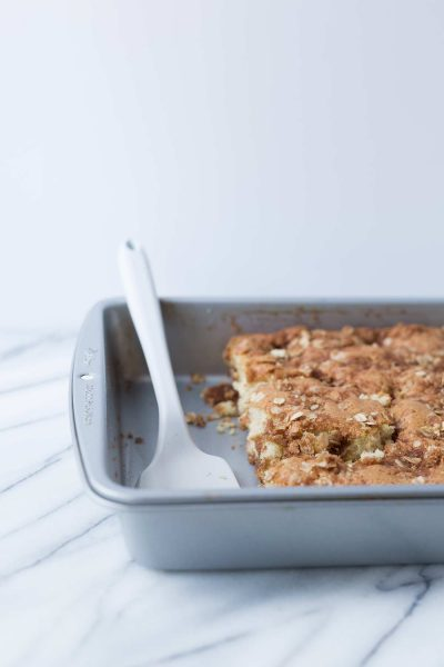 white serving spatula in baking pan with cinnamon streusel coffee cake