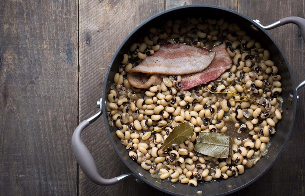 A photo of a pot of black eyed peas cooking with herbs and a slice of bacon
