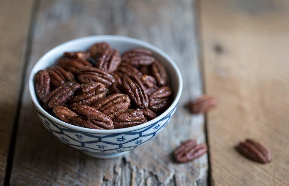 A close up photo of candied pecans.