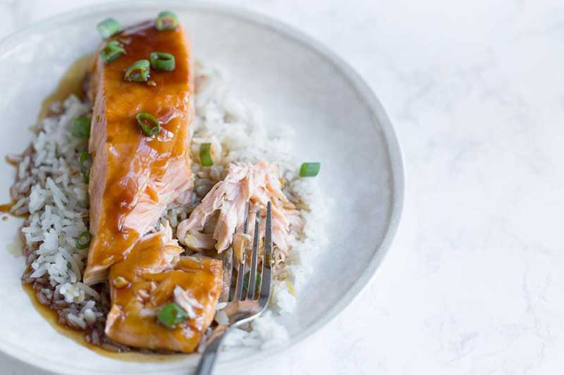 baked teriyaki salmon on a plate with white rice and a fork