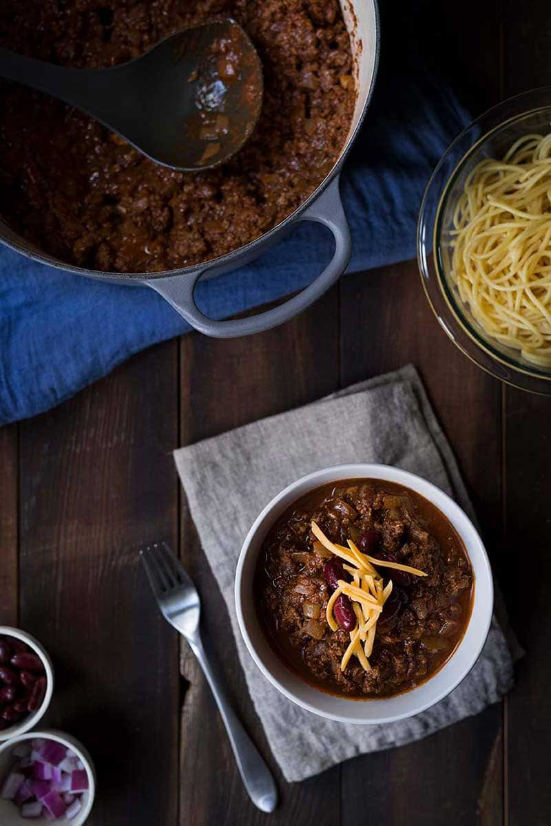 Cincinnati chili recipe in a bowl, surrounded by various toppings and a full batch of chili