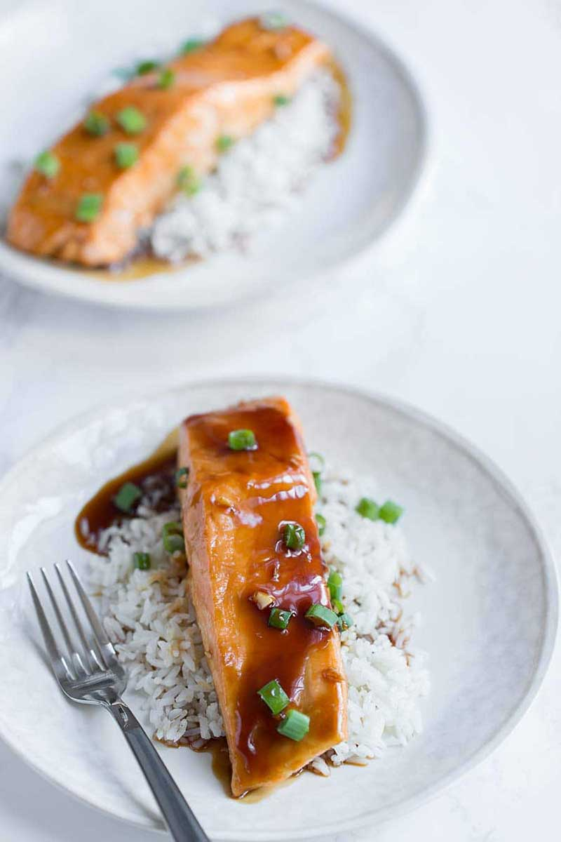 two baked teriyaki salmon filets on white plates with rice