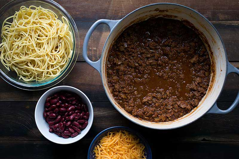 Cooked Cincinnati chili recipe in a Dutch oven, surrounded by classic garnishes.