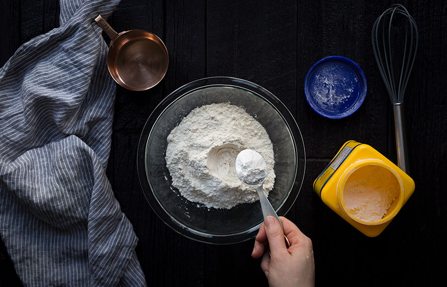 A photo of flour in a bowl with 1 tablespoon of cornstarch being added.