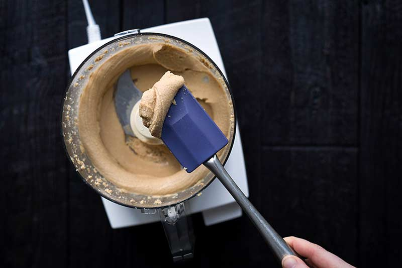 overhead photo of a creamy nut spread in the bowl of a food processor, with some on a spatula