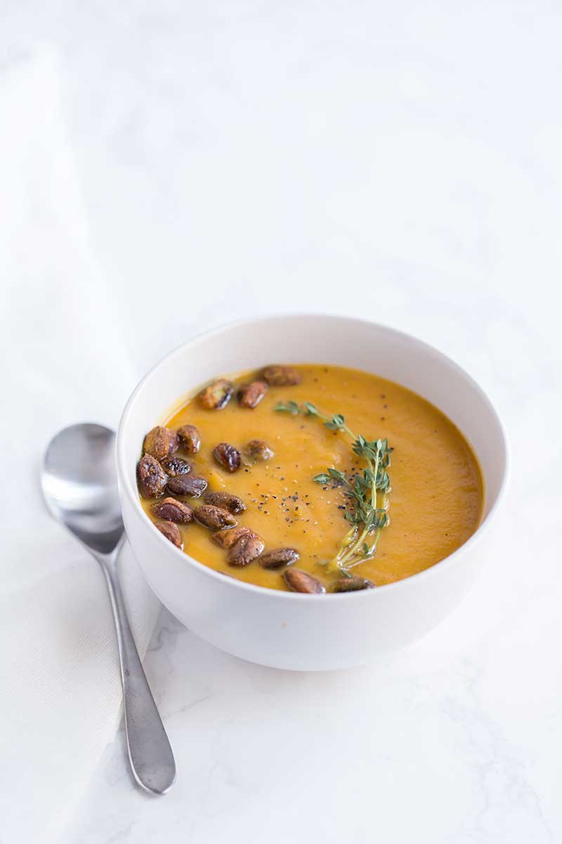 roasted butternut squash soup recipe garnished with pistachios, thyme, and black pepper