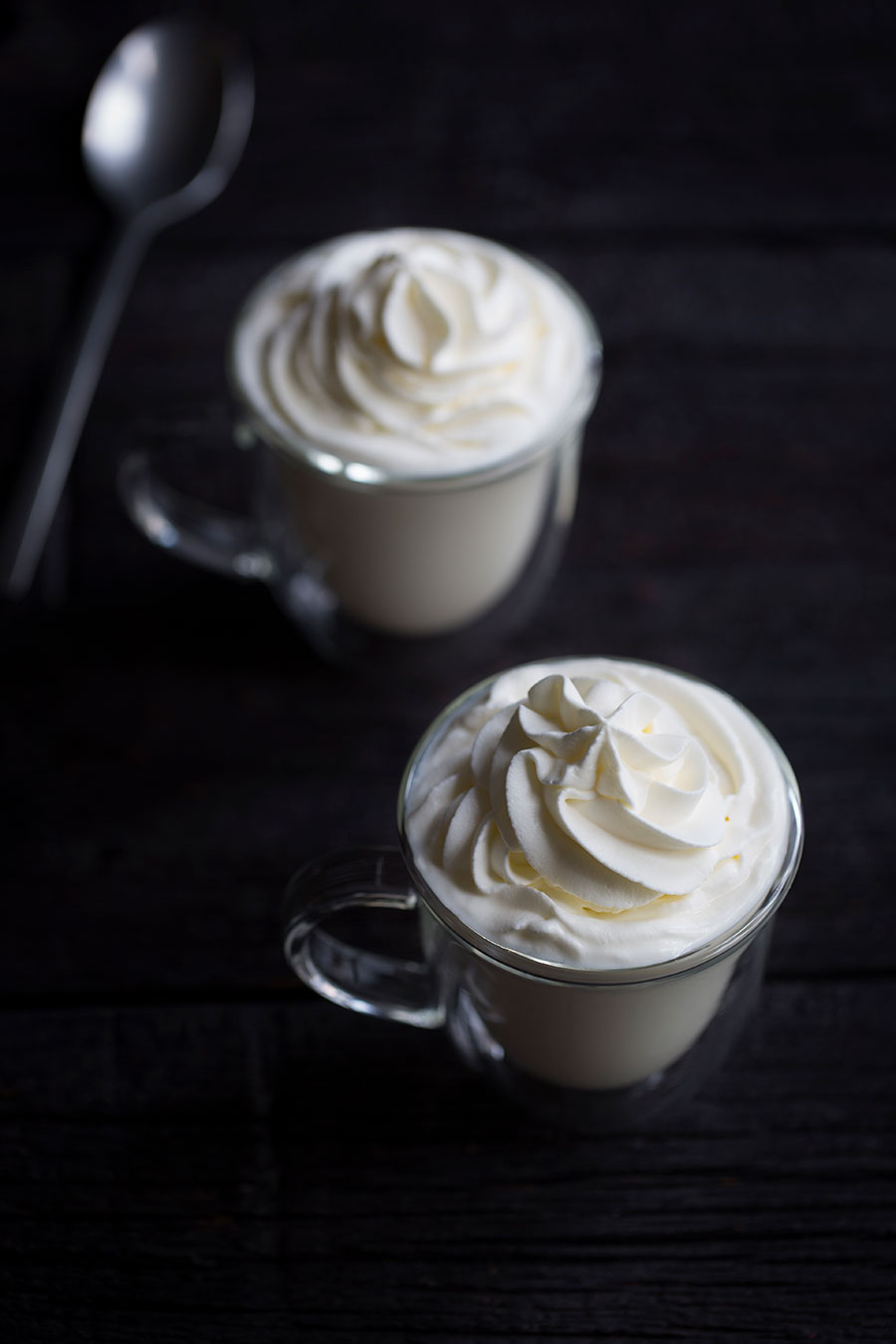 A close up photo of white hot chocolate on a dark backdrop.