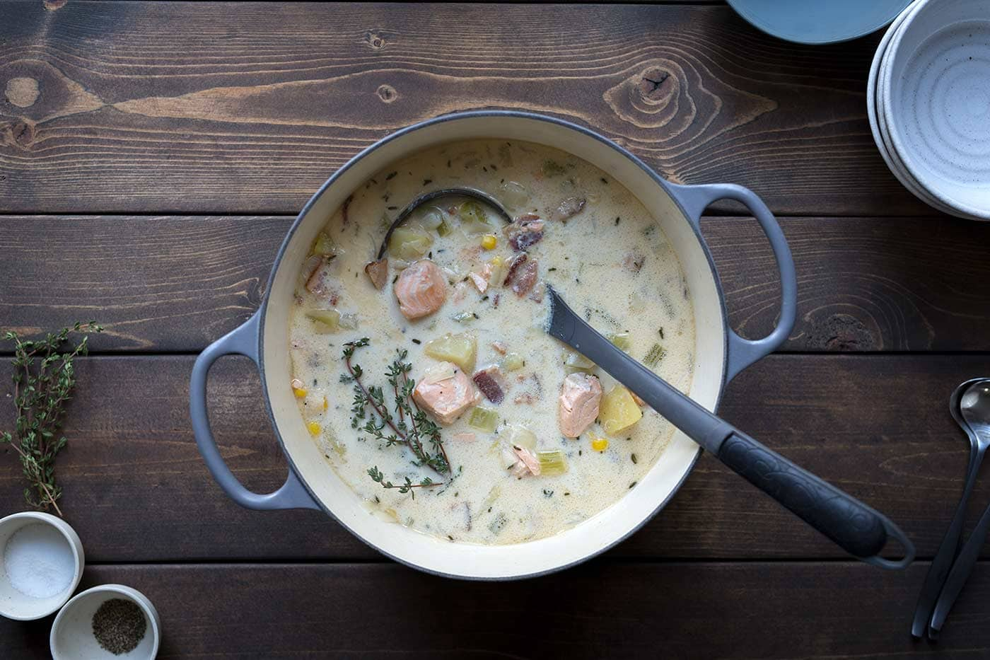 Salmon chowder in a large pot showcasing some of the various ingredients, including potatoes and bacon.