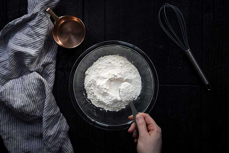 A photo of AP flour in a bowl with 1 tablespoon being removed.