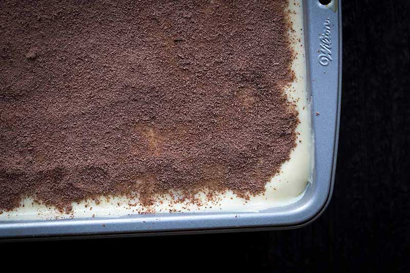 cocoa powder dusted over custard layer of homemade tiramisu