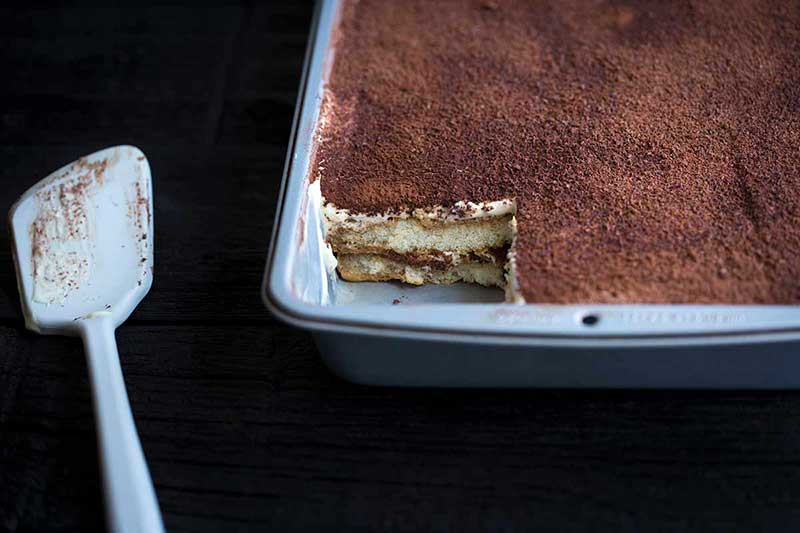 Tiramisu in a baking pan with one slice missing and a spatula