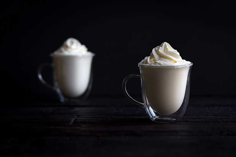 Two cups of white hot chocolate recipe topped with whipped cream.
