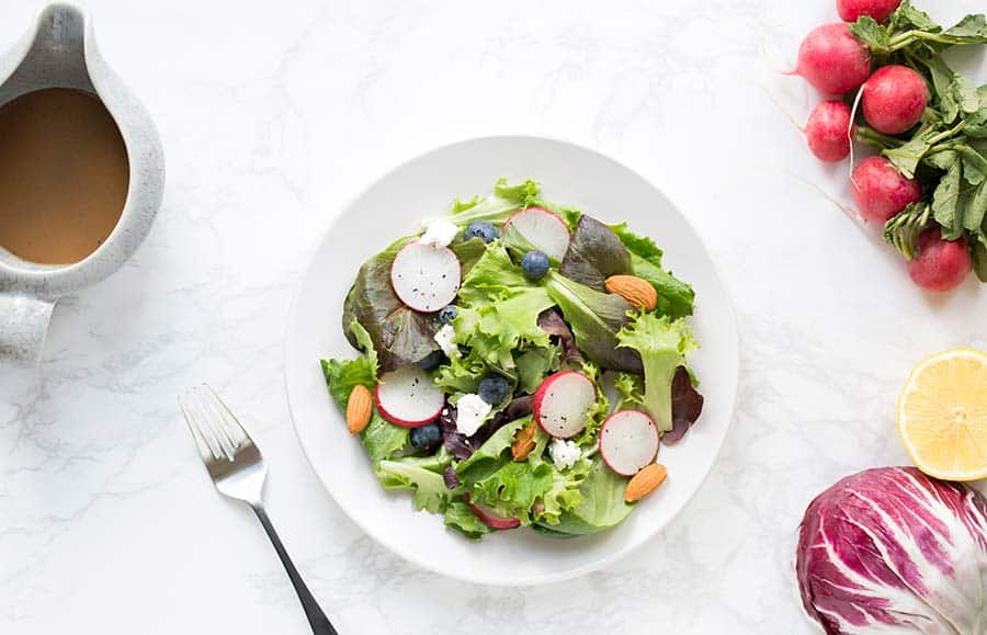 A colorful salad surrounded by vibrant vegetables.