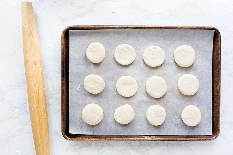 A sheet pan lined with parchment paper, topped with 12 raw buttermilk biscuits.