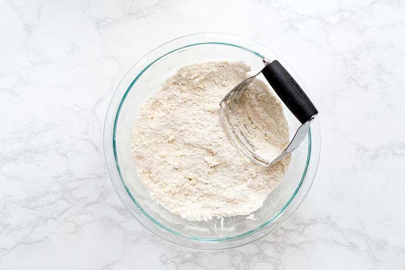 Combining biscuit recipe ingredients in a bowl with a pastry blender to keep the butter cold.