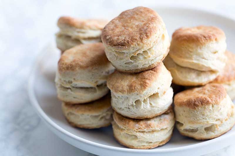 A photo of the finished buttermilk biscuits stacked high on a serving plate.
