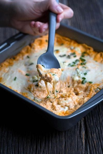 Buffalo chicken dip being scooped with a spoon. Oozing cheese dripping back into the pan.