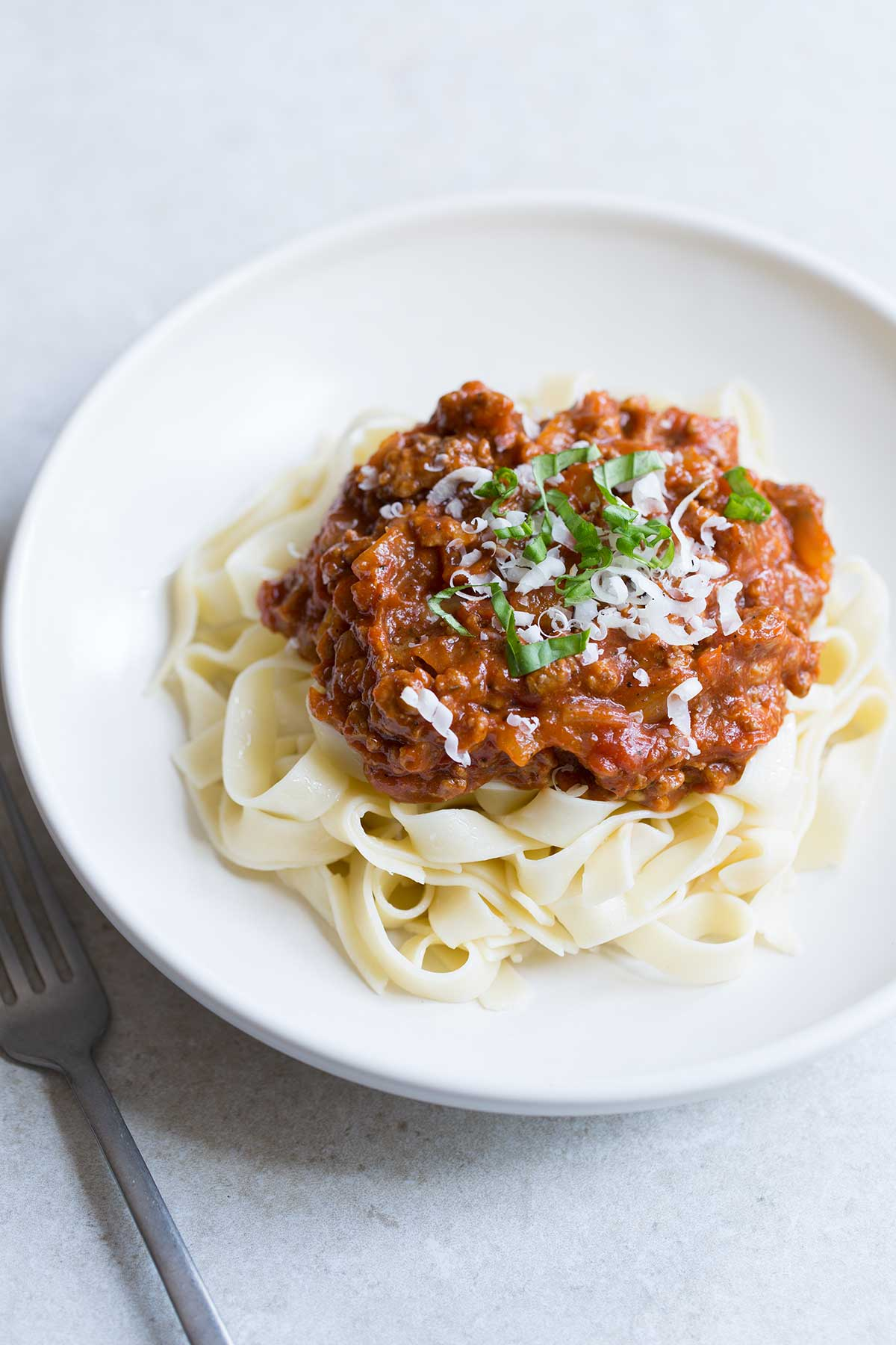 A meat sauce recipe served over pasta in a bowl, topped with fresh grated parmesan and sliced basil.