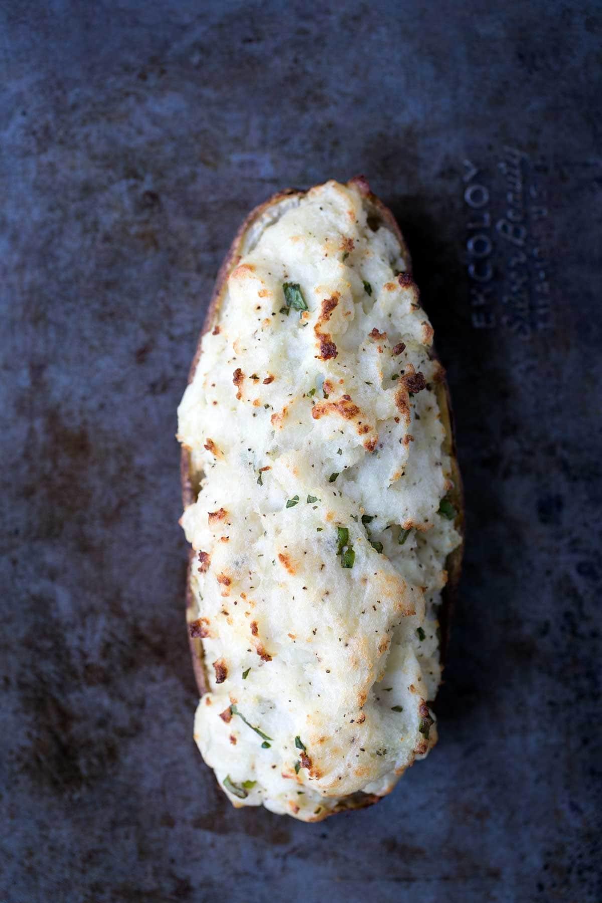 An overhead shot of a single twice-baked potato on a baking sheet.