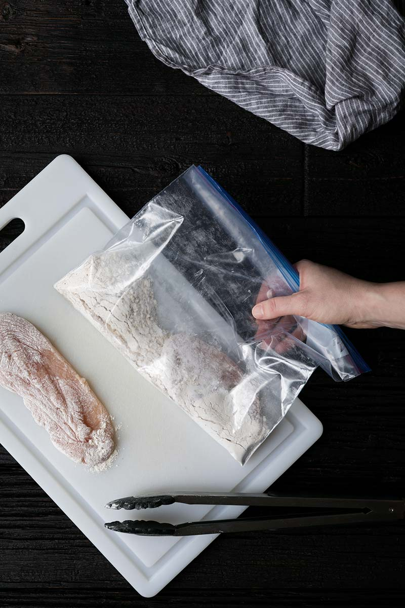 Chicken breasts that have been dredged in a mixture of flour, salt and pepper using a resealable plastic bag.