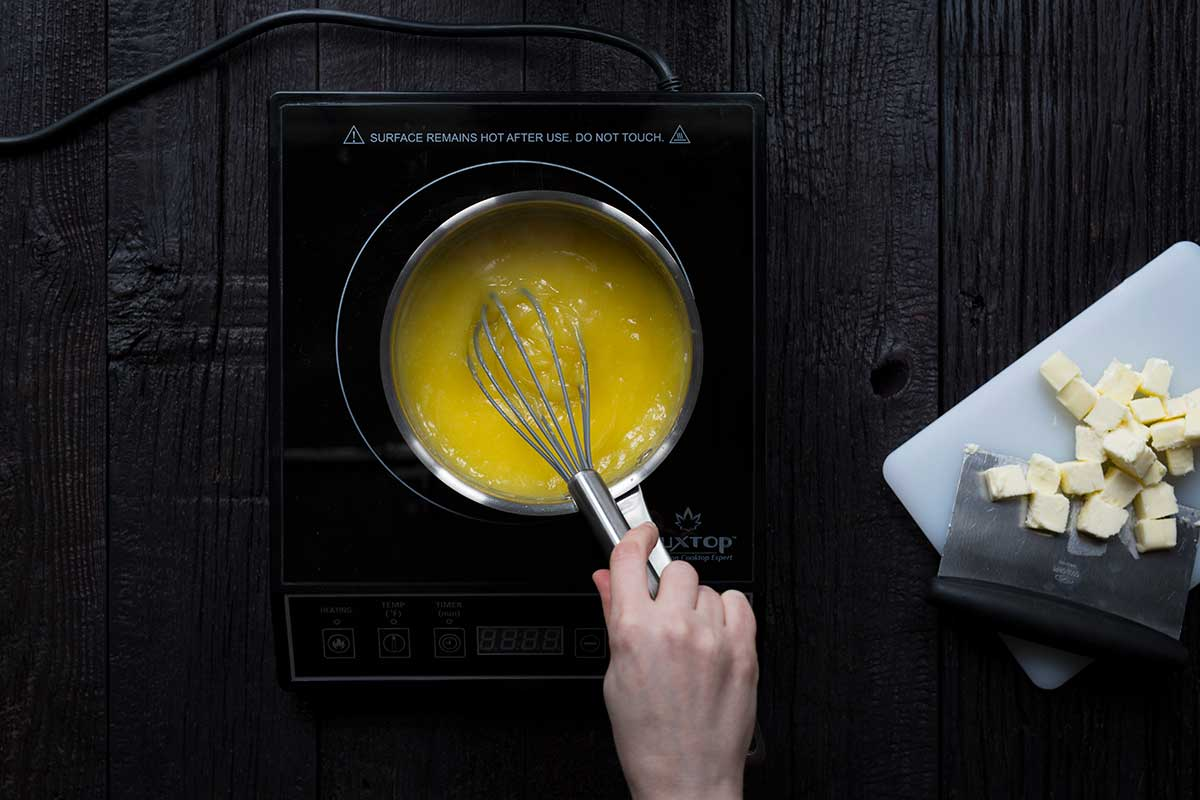 Whisking the lemon curd ingredients together until thick.