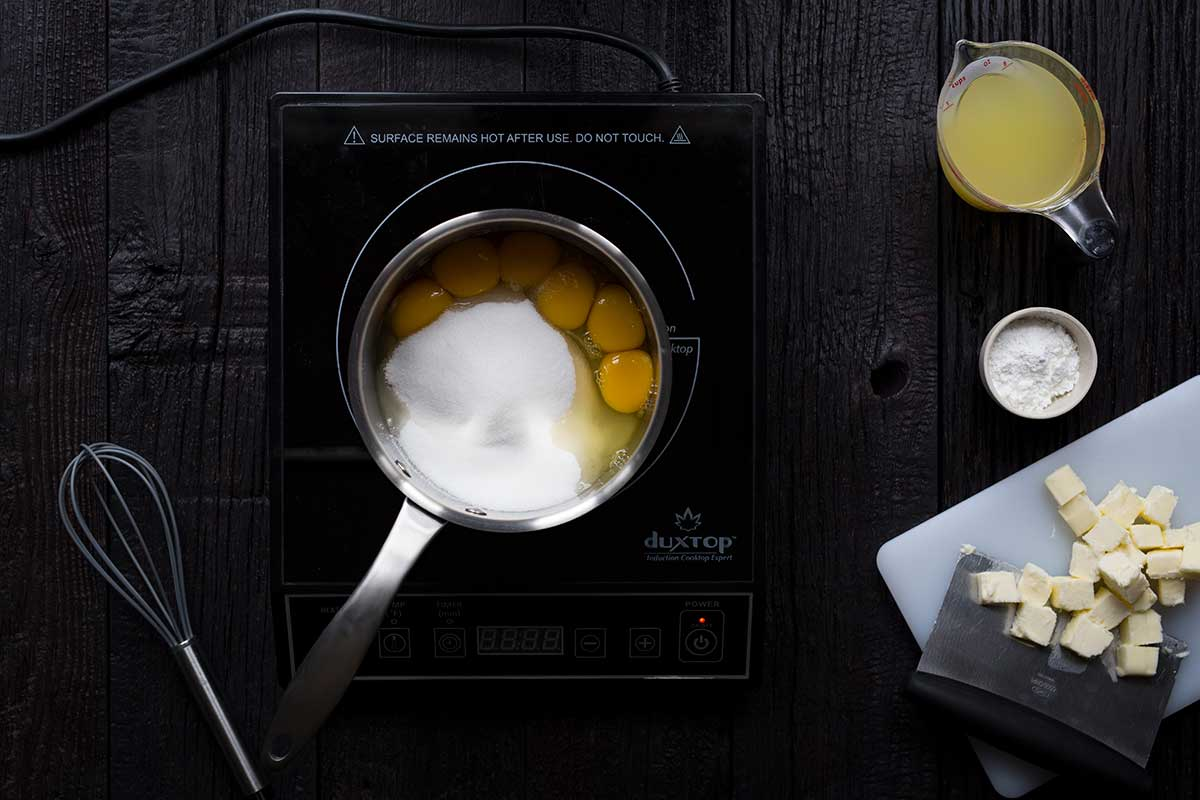 An induction burner topped with a saucepan filled with eggs and sugar, surrounded by butter, lemon juice and cornstarch.