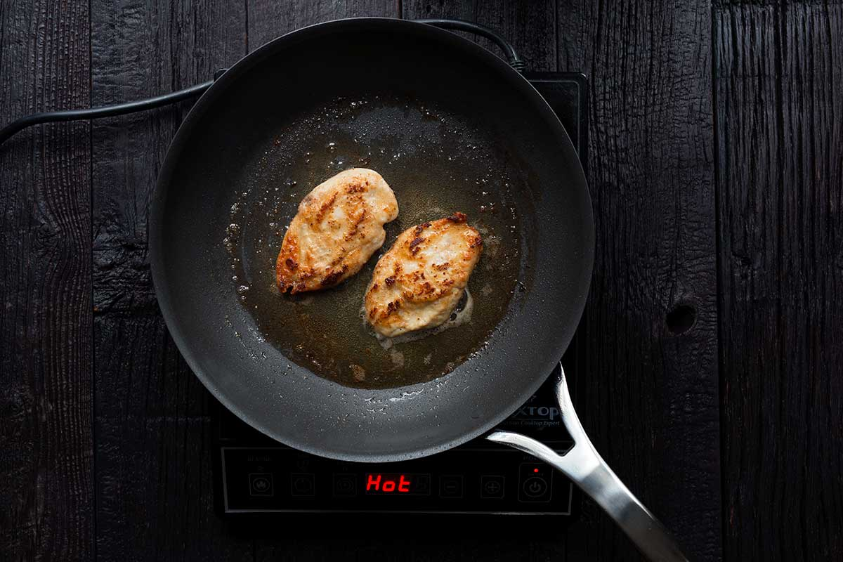 Chicken breasts pan frying in a large skillet.