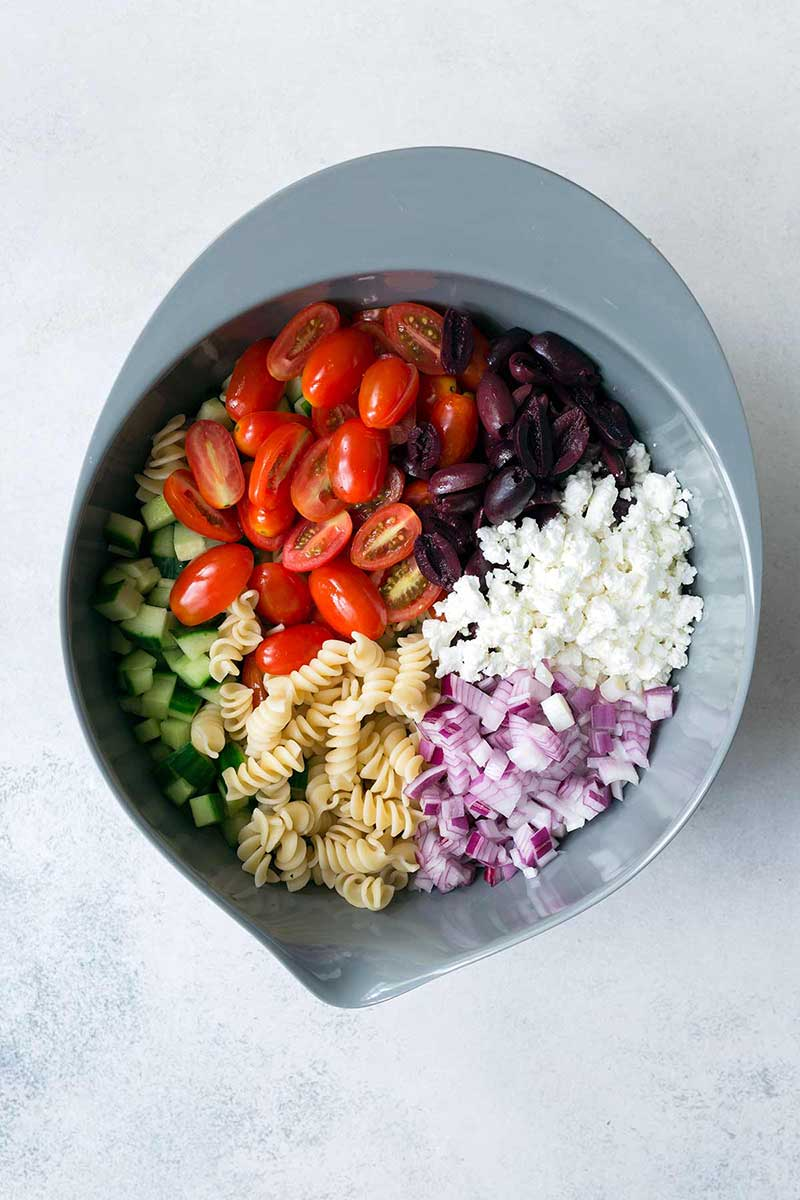 overhead image: ingredients in a stainless steel mixing bowl to make a Mediterranean pasta salad recipe
