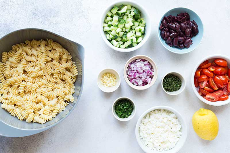 summer salad recipe ingredients, including cooked pasta, cucumbers, olives, tomatoes, red onions, garlic, and feta cheese.